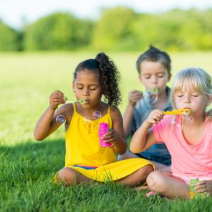 3 kids blowing bubbles