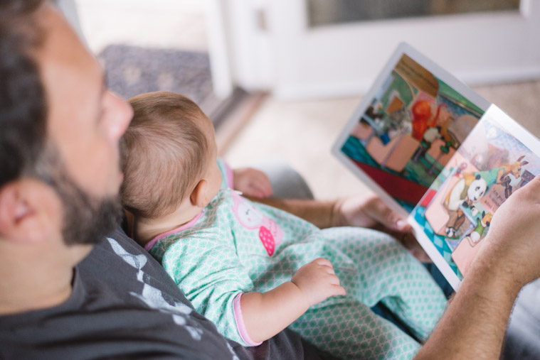A father and his infant daughter look at a book together