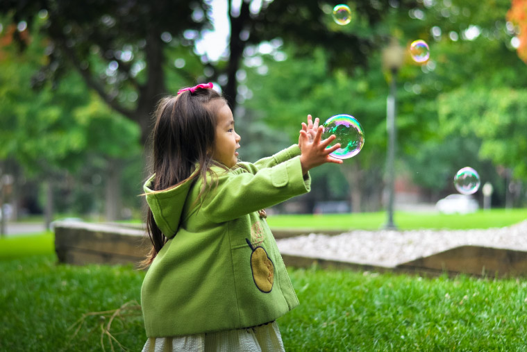A girl in a green coat stands in a park trying to catch bubbles