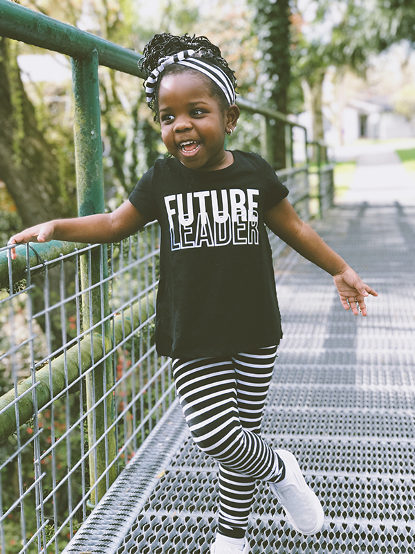 A young girl stands on a bridge wearing a shirt that says Future Leader highighting Ready Ready's committment to the future.