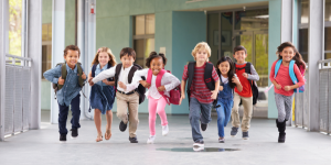 Young children with school backpacks running toward the camera with smiles on their faces