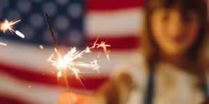 Girl holding sparkler, american flag,