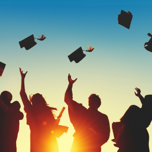 silhouettes of people throwing graduation caps in the air